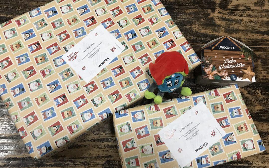 auf dem Tisch liegen zwei Geschenke und das WOGETRA Maskottchen