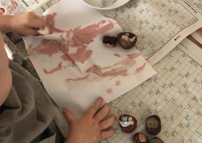 Kind bastelt mit Farbe und Kastanien