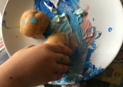Kind bastelt mit Farbe und einer Kartoffel
