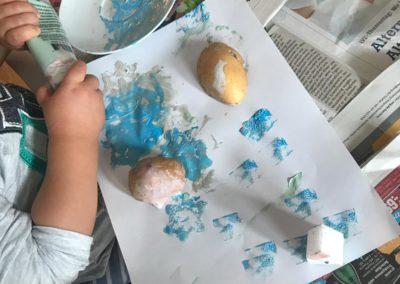 Kind malt mit Farbe und macht Stempel mit bemalten Kartoffeln