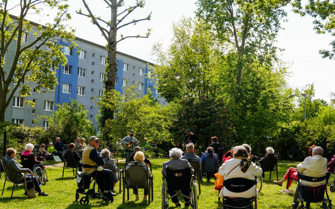 Ältere Personen sitzen im Park und schauen das Konzert auf dem Johannisplatz