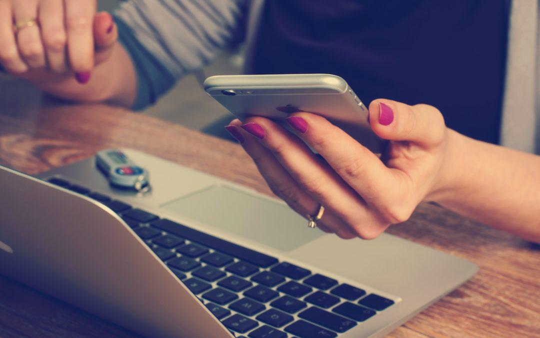 Frau hält Telefon und Laptop steht auf dem Tisch