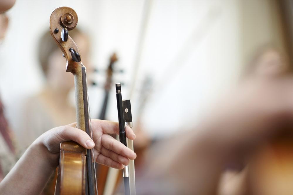 Geigen in Händen von Musikern
